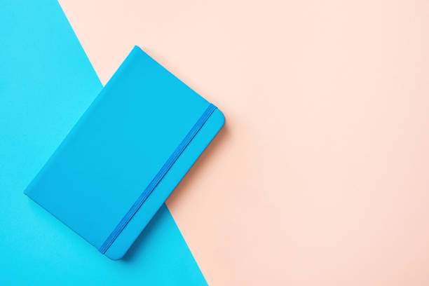 unternehmen bildung hintergrund tagesplaner mit gummiband auf duotone blau rosa hintergrund. minimalistischen stil. selbständiger unternehmerinnen konzept blog stationäre verkaufsbanner. mock-up mit textfreiraum - unterrichtsplanung vorlagen stock-fotos und bilder