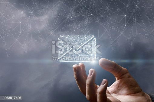 Business email concept. The hand shows a hologram of a letter on a blurred background.