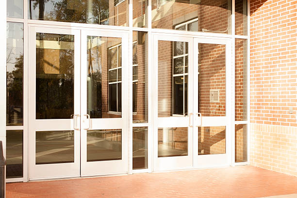 business: empty office building, school.  front doors are closed. - entrance stock photos and pictures