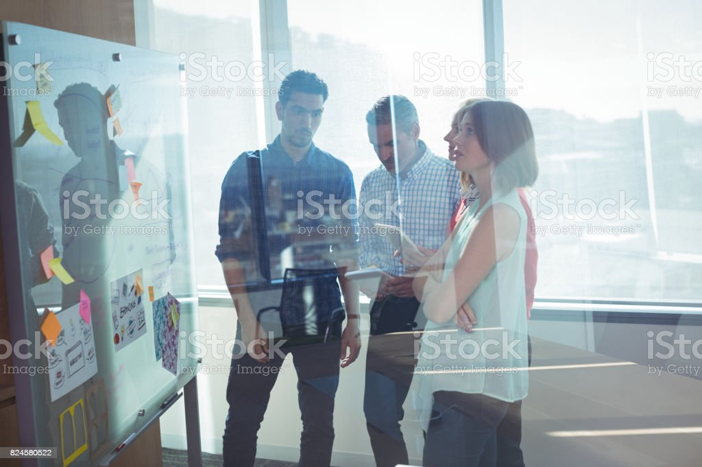Business entrepreneurs standing by whiteboard seen through glass stock photo