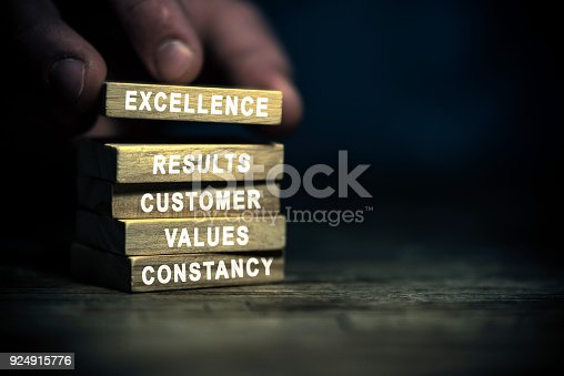 Hand in the dark building with wood blocks that have printed on the side white words related to business excellence concept