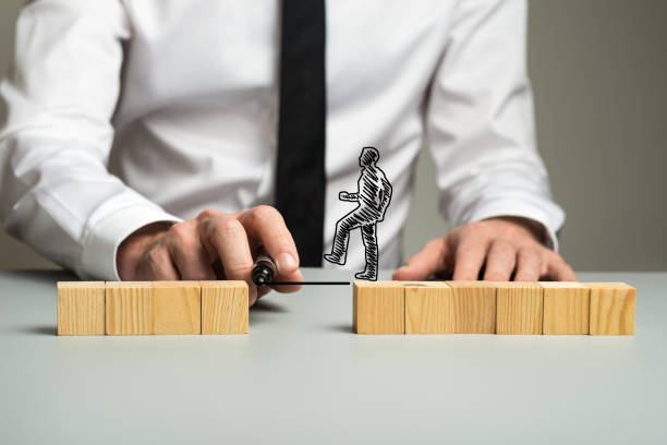 Business executive drawing a line for a silhouetted businessman stock photo