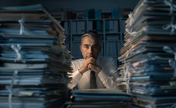 Business executive overloaded with work Stressed exhausted business executive working in the office late at night with piles of paperwork, he is overloaded with work: management and deadlines concept bureaucracy stock pictures, royalty-free photos & images