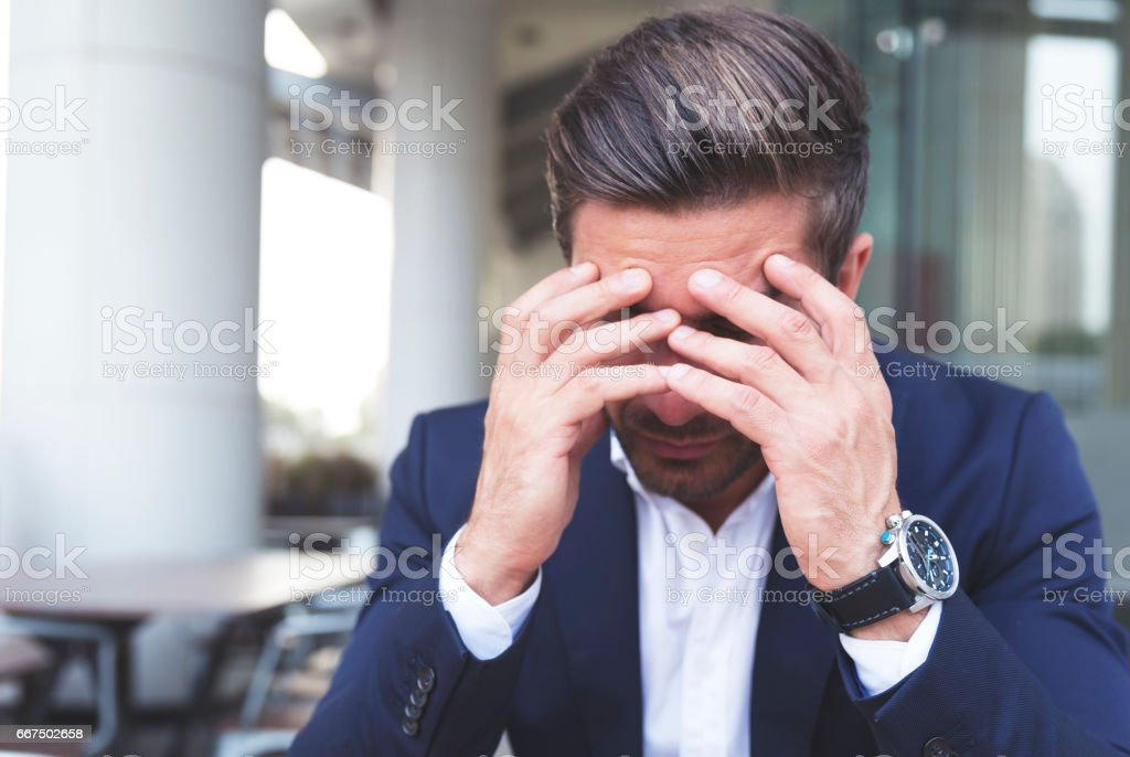 Business executive seated outside his office after being laid off stock photo