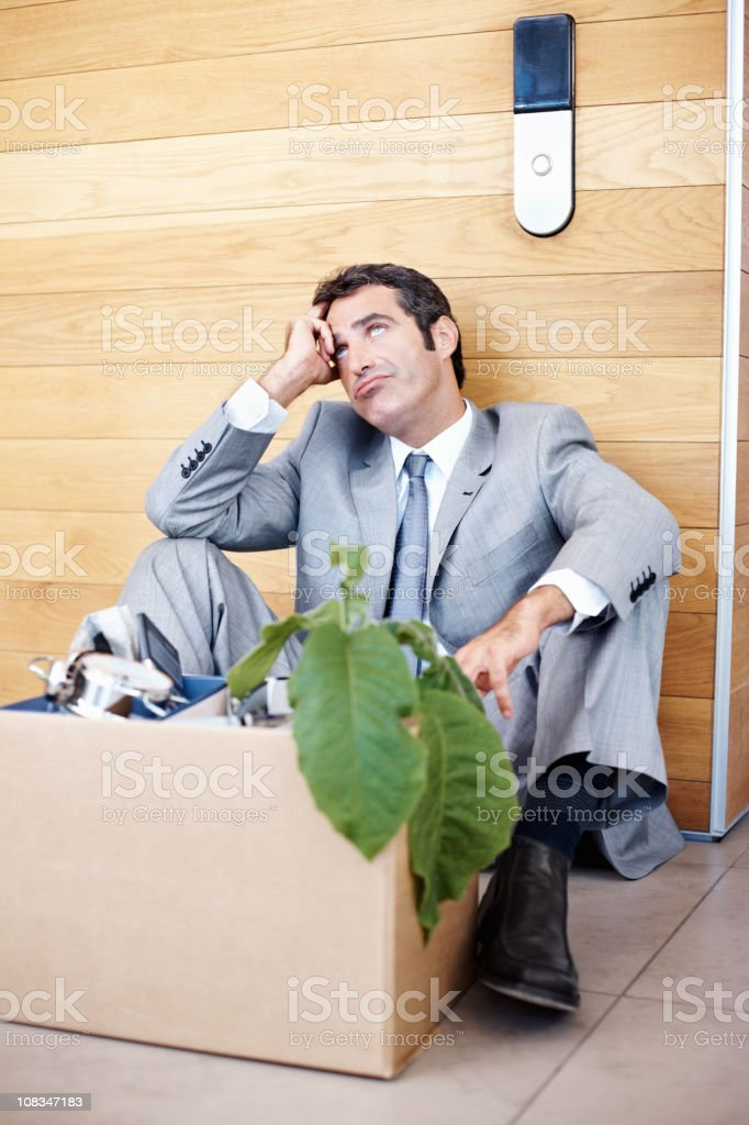Business executive sitting with a box of office material royalty-free stock photo