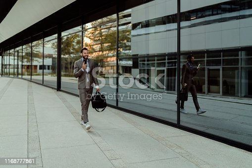 Businessman Using Mobile Phone App Texting Outside of Office in Urban City With Skyscrapers Buildings in the Background. Young Caucasian Man Holding Smartphone for Business Work. Motion Image of Young Business Executive Smartly Dressed With Mobile Phone at Airport.