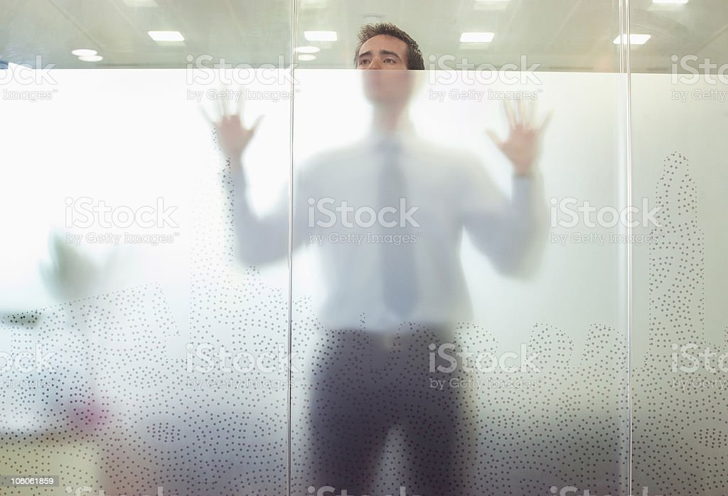 Business executive standing behind glass door stock photo