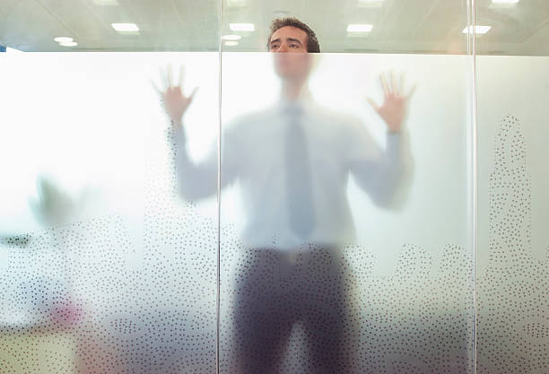 business executive standing behind glass door - trapped stock pictures, royalty-free photos & images