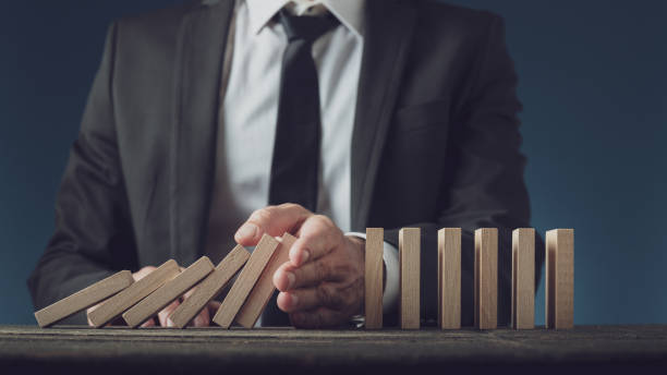 Business Executive stoppt kollabierende Dominos mit der Hand – Foto
