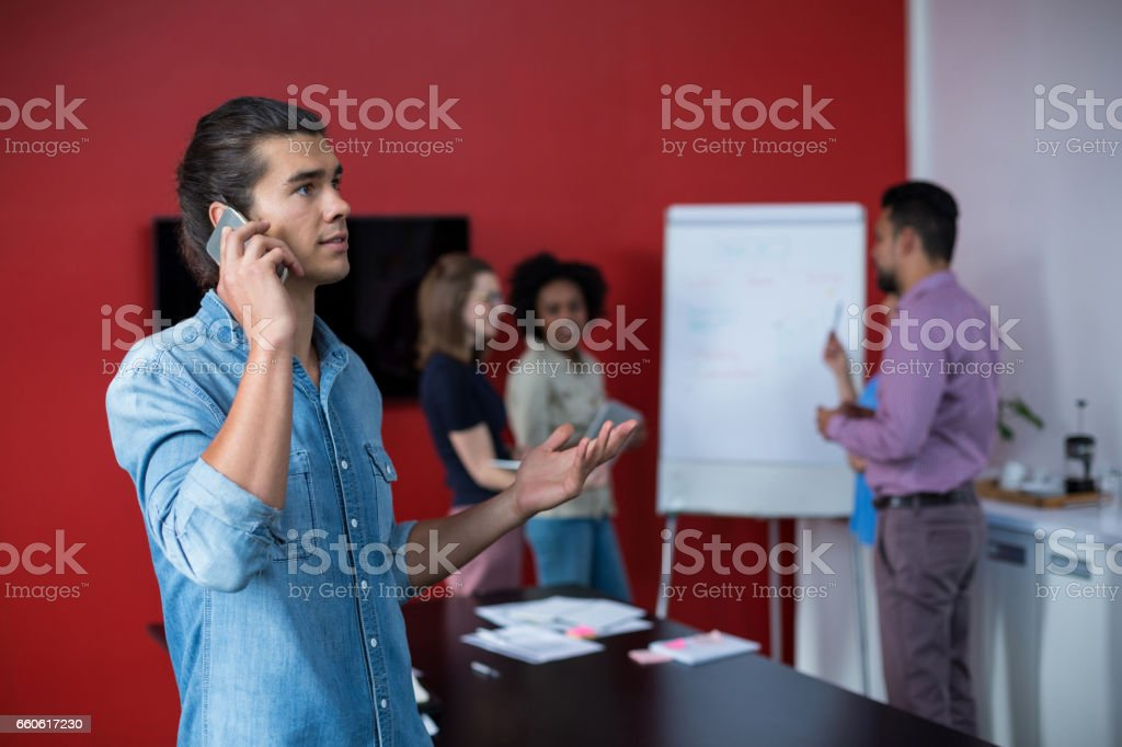 Business executive talking on mobile phone at meeting royalty-free stock photo