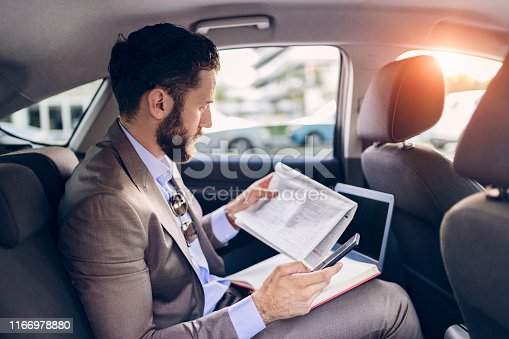 Confident Man in Full Suit Reading Newspaper and Using Smart Phone While Sitting in the Car on the Back Seat With Cityscape in the Background. Transport, Business Trip, Paperwork and People Concept