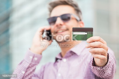 Cheerful businessman talking on the mobile phone and showing credit card in front of business building.
