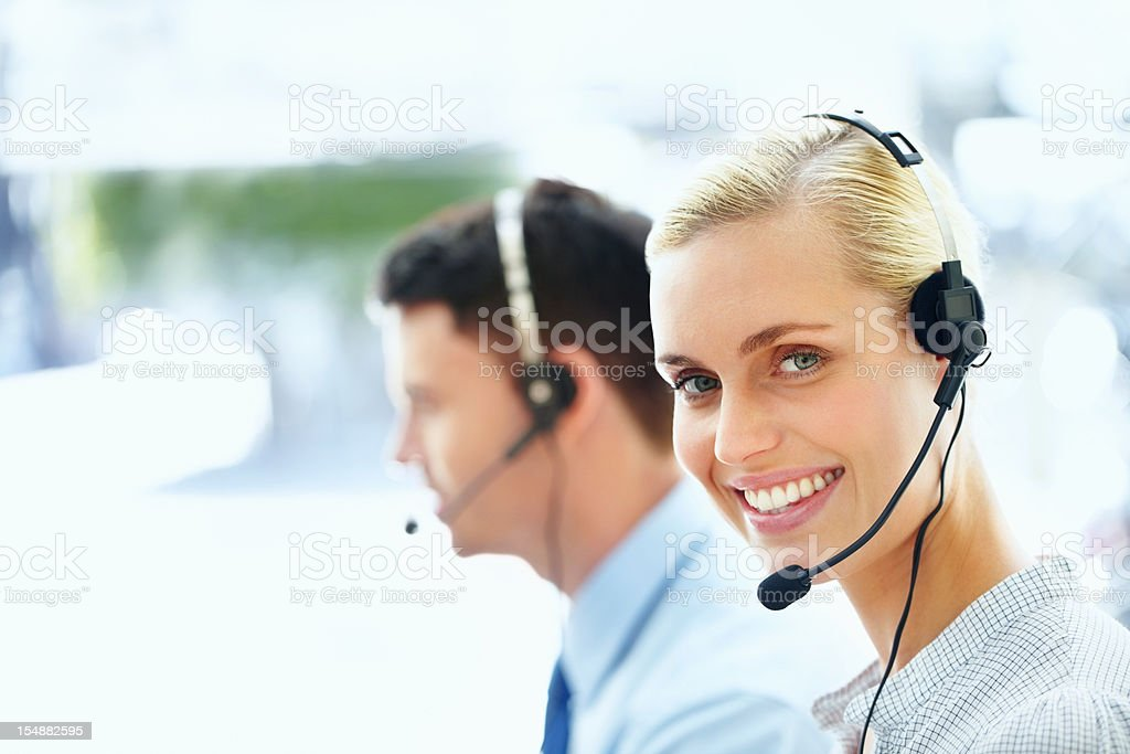 Business executive wearing headset with colleague in background royalty-free stock photo