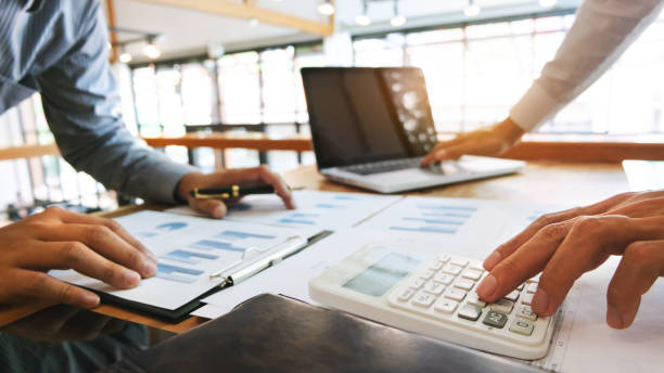 Business executives analysis data document and calculating about fee tax at a office stock photo