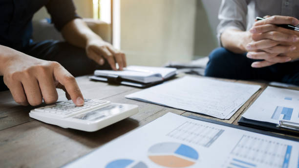 Business executives analyzing on valuation data paper with calculator stock photo