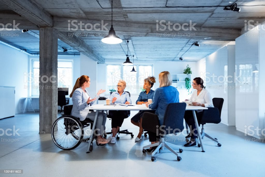 Business executives brainstorming in new office Business executives brainstorming at desk. Disable businesswoman is talking with colleagues while sitting on wheelchair. They are working in new office. 35-39 Years Stock Photo