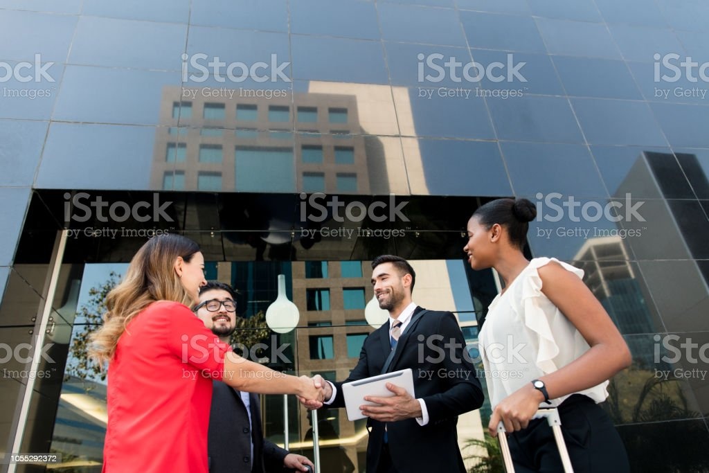 Business executives closing deal in front of building stock photo