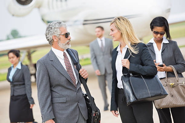 Business executives deboarding private jet stock photo