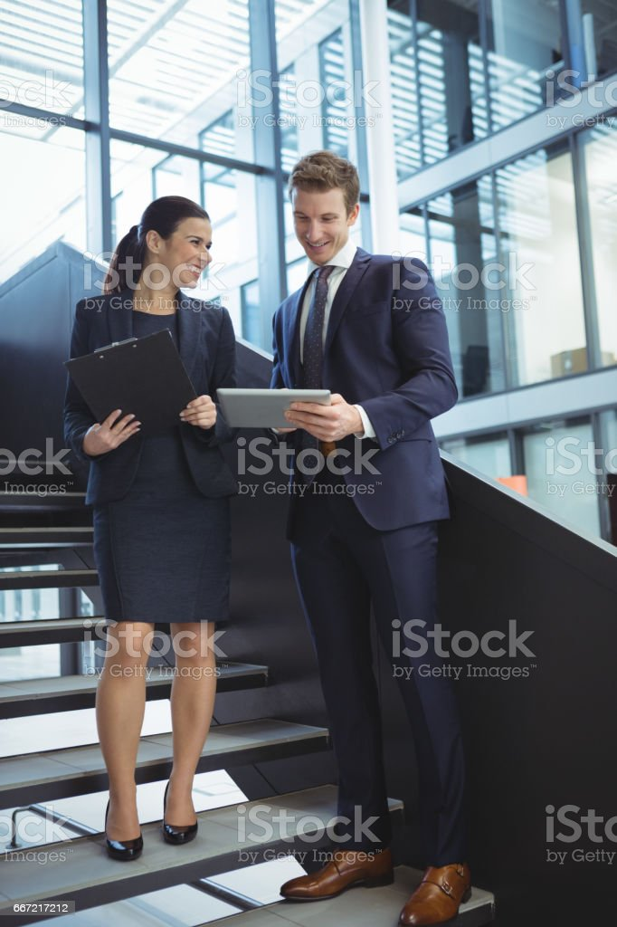 Business executives discussing over digital tablet on stairs stock photo