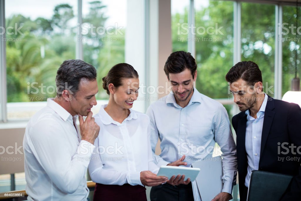 Business executives discussing over digital tablet stock photo