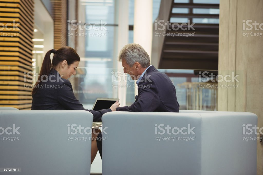 Business executives discussing over laptop royalty-free stock photo