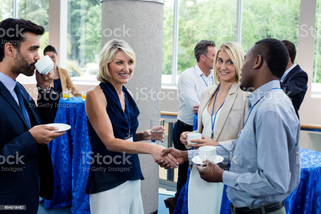 Business executives interacting with each other while having coffee stock photo