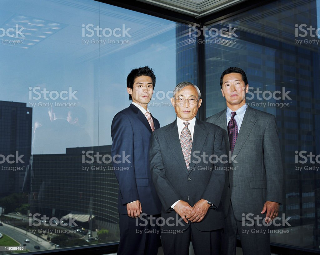 Business executives standing next to window in office, portrait royalty-free stock photo