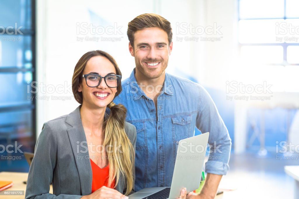 Business executives standing with a laptop stock photo