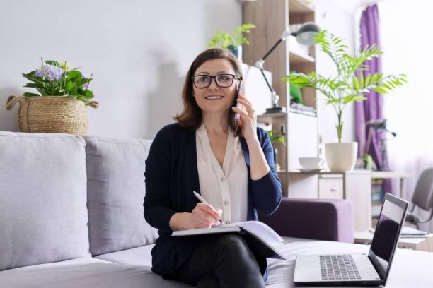 İş kadın serbest dizüstü bilgisayar ile kanepede oturan, telefonda konuşurken stok fotoğrafı