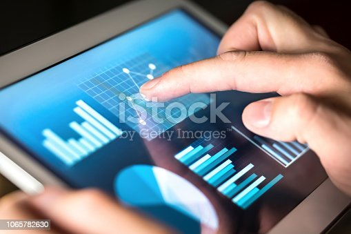 istock Business figures, graphs, chart and statistics. Market or economic report for financial analysis. Man working and using tablet. Finger touching screen. 1065782630