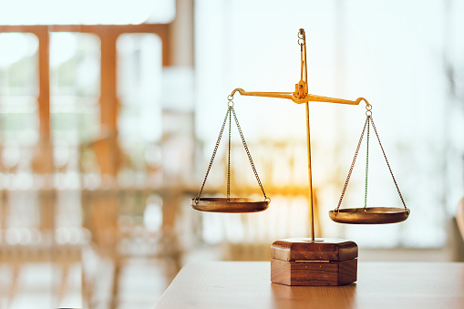 Symbol of law and scales of justice on wooden table in Legal office