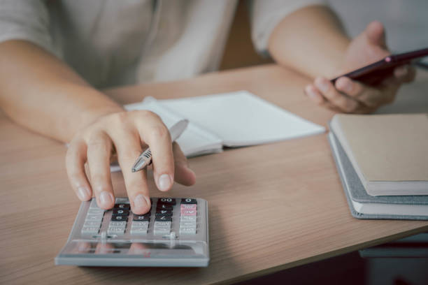 Business & Finance concept. Close up hand of young Asian man wear white shirt ongoing to calculate home loan mortgage to summary expense payment or accounting with using smartphone on office deck stock photo