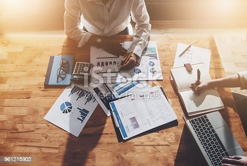 950986656istockphoto business finance meeting , Businessman and Businesswoman to data analysis budget marketing of company with using calculator laptop computer notebook and document data in working . 961215902