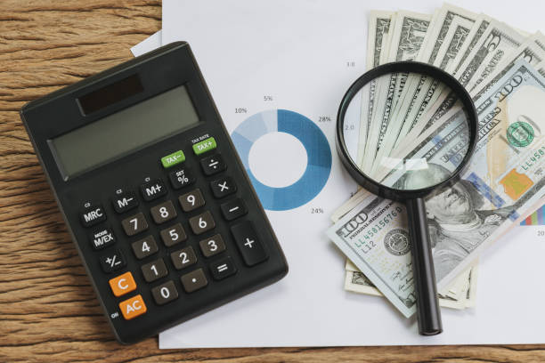 Business, financial, accounting or tax analyze concept, office calculator on color pie chart diagram with magnifying glass on pile of US dollar banknotes on wooden table - foto stock