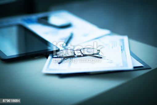 istock Business financial analysis of the workplace with the glasses on the documents 879618684