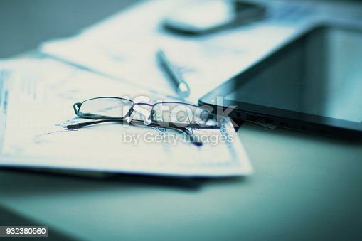 istock Business financial analysis of the workplace with the glasses on the documents 932380560