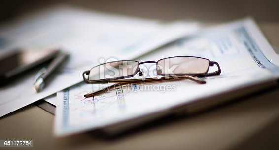 istock Business Financial Analysis workplace, glasses lie on documents 651172754