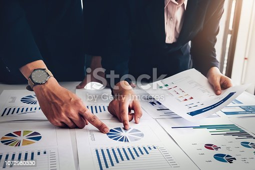 1032388356istockphoto Business financial, Business accountant using computer laptop and discussing with partner are meeting to audit finance planning sales to meet targets set in next year. budget plan concept. 1072980330