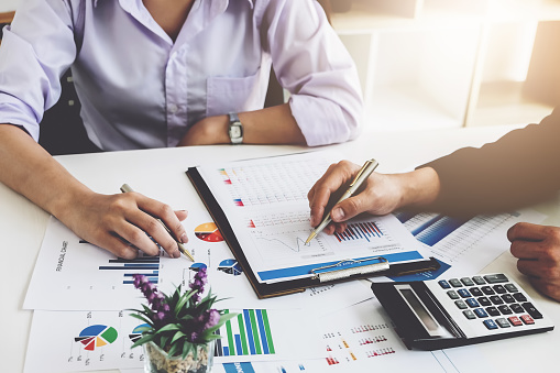 Business Financial Concept Busines Sman And Partner Pointing Graph Paper Are Meeting To Plan Sales To Meet Targets Set In Next Year Stock Photo - Download Image Now