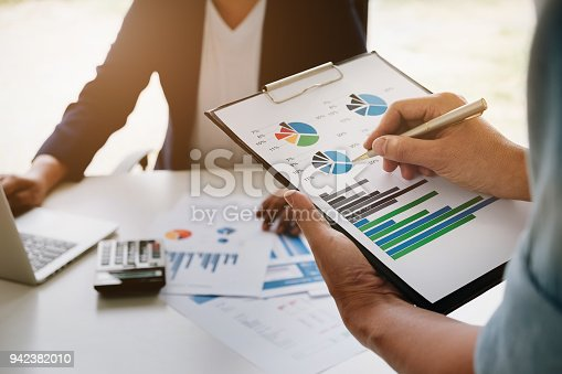942382022istockphoto Business financial concept,consult partner hand holding pen point stock marketing document and business man owner using computer laptop in office. 942382010