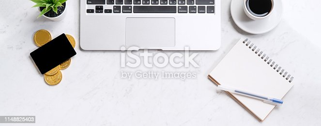 istock Business financial design concept, marble white office table desk top view with smart phone, mockup credit card, coins, laptop, flat lay, copy space 1148825403