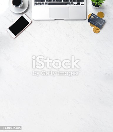 1060760900istockphoto Business financial design concept, marble white office table desk top view with smart phone, mockup credit card, coins, laptop, flat lay, copy space 1148825405