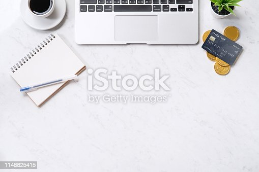 istock Business financial design concept, marble white office table desk top view with smart phone, mockup credit card, coins, laptop, flat lay, copy space 1148825415