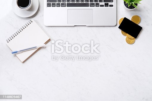 istock Business financial design concept, marble white office table desk top view with smart phone, mockup credit card, coins, laptop, flat lay, copy space 1148825467