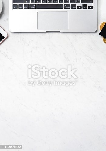 1060760900istockphoto Business financial design concept, marble white office table desk top view with smart phone, mockup credit card, coins, laptop, flat lay, copy space 1148825468