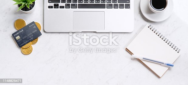 1060760900istockphoto Business financial design concept, marble white office table desk top view with smart phone, mockup credit card, coins, laptop, flat lay, copy space 1148825471