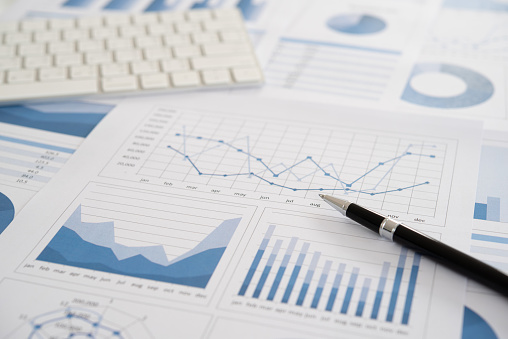 pen with business report and financial statement on desk of data analyst.