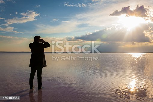 Business man looks through binoculars, Salt Lake-Turkey.