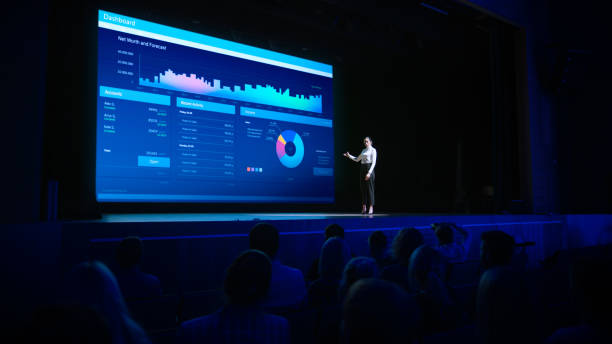 business forum economics conference stage: visionary female chief analyst delivers speech and shows infographics, statistics on movie theater screen. presentation with speaker in full auditorium hall - theatre full of people stage foto e immagini stock