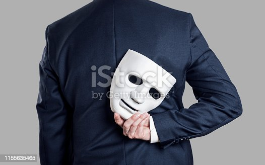 istock Business fraud concept. Businessman hide the mask in hand behind his back. 1155635465
